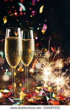 Two bright icy champagne glasses, confetti falling and sparklers - stock photo