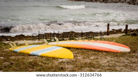 Two bright  surfboards lying at the sea sand close up - stock photo