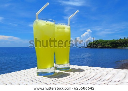 Two bright yellow lemon pineapple tropical drinks. Blue sunny sky with clouds, calm water, romantic cocktail beach scenery.