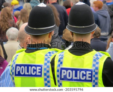 Two British policemen watching during crowded street event - stock photo