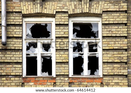 Two broken windows of the old abandoned brick building - stock photo