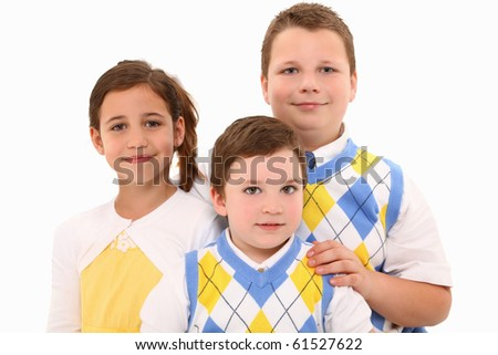 Two brothers and sister in matching outfits over white background. - stock photo