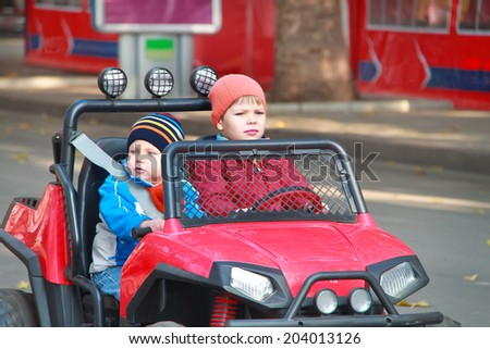 Two brothers are driving the red car - stock photo