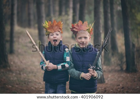 Two Brothers cuddling  in a forest on autumn day. Little kids hugging. - stock photo