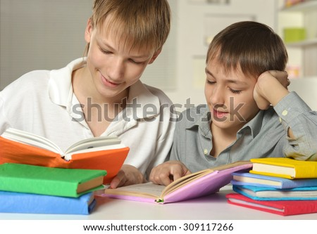 Two brothers doing homework at home at table - stock photo