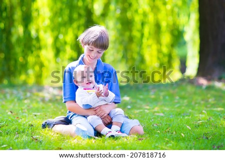 Two brothers, happy school age boy and a little baby, playing together sitting on the lawn smelling daisy flowers enjoying a warm sunny day in the garden