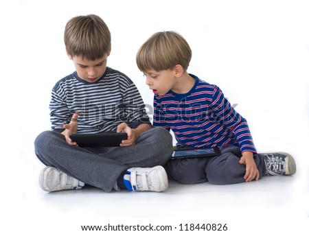 two brothers playing games on the tablets - stock photo