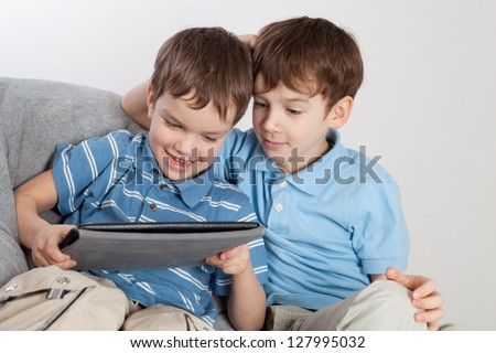 Two brothers playing on tablet, indoor - stock photo