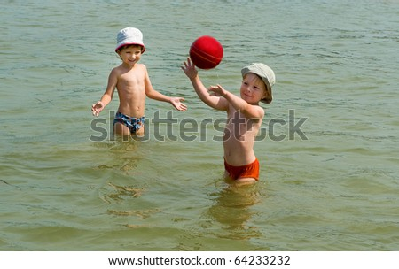 two brothers playing with ball in the water