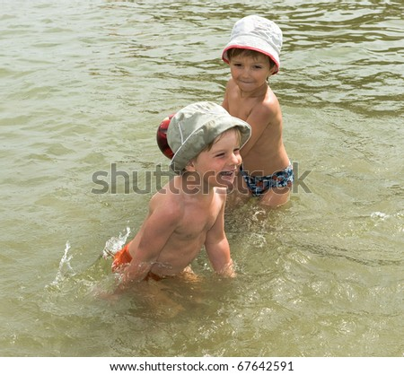 two brothers playing with ball in the water - stock photo