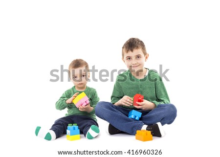 Two brothers playing with colorful cubes on the floor over white