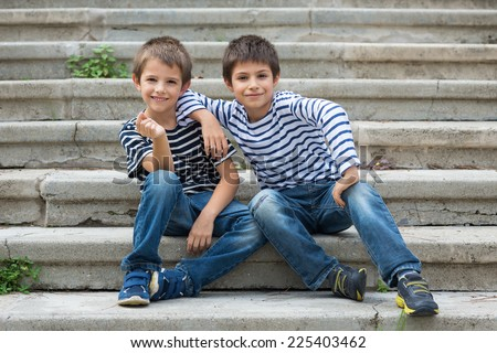 Two brothers portrait having fun sit on stairs outdoors. - stock photo
