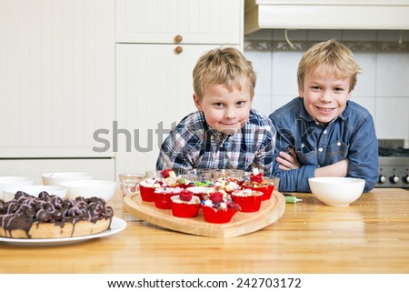 Two brothers posing in a kitchen, together in front of a heart shaped cutting board with freshly baked and decorated cupcakes  - stock photo