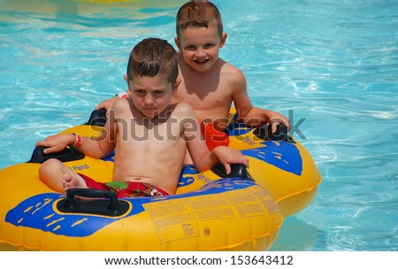 Two brothers ride the tube through the water on a hot summer day - stock photo