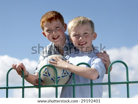 Two brothers standing by railing after playing football in the park - stock photo