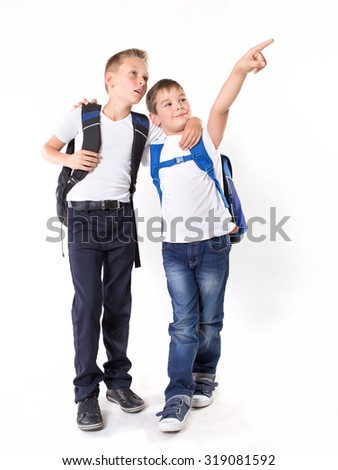 Two  brothers standing together with backpack hugging, full height portrait isolated on white