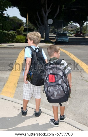 Two brothers watch for traffic at a crosswalk to ensure their safety - stock photo