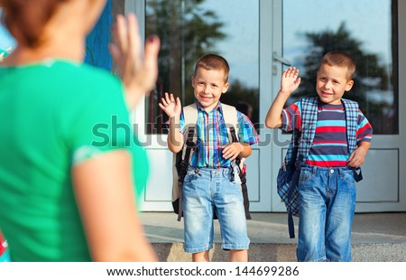 Two brothers waving back at their mother on their first day at school. - stock photo