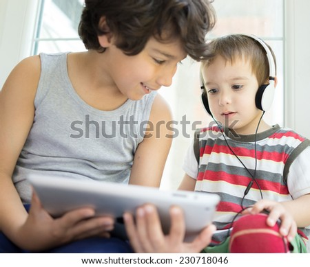 Two brothers with tablet at home - stock photo