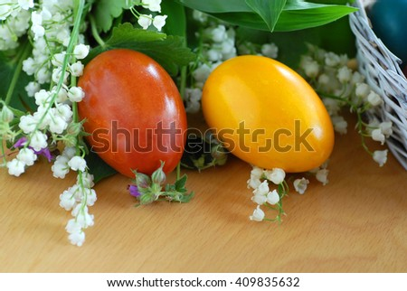 two brown and yellow easter eggs on the table with may-lily flowers - stock photo