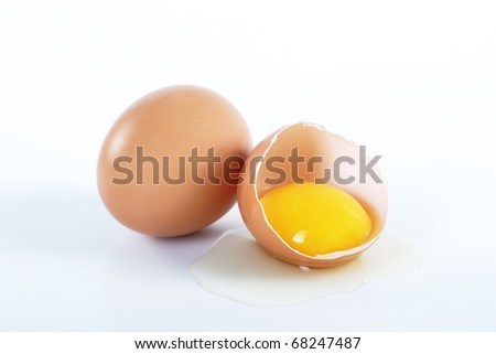 Two brown eggs on a white background. One egg is broken. - stock photo