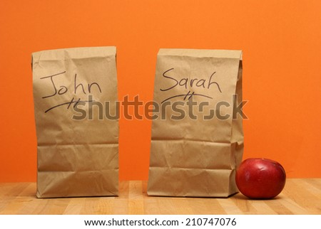 Two brown lunch bags prepared specially for John and Sarah. - stock photo