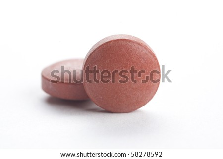 two brown pills, isolated on white - stock photo