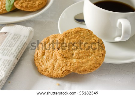 Two brown wholemeal biscuits with a white cup and saucer - stock photo