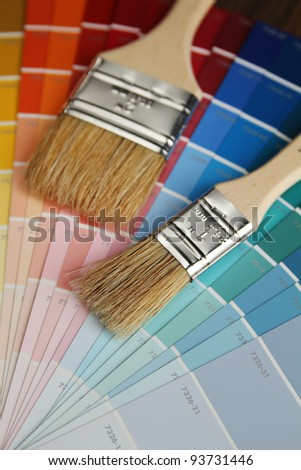 Two brushes with wood handle on a color guide - stock photo