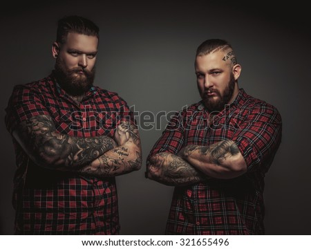 Two brutal mans with beards and tattoo isolated on grey background. Crosed arms. - stock photo