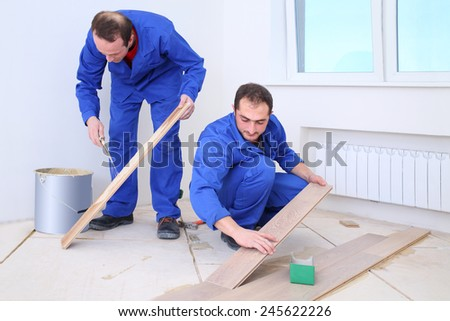 Two builders apply glue to the board with a spatula and put them on the floor - stock photo