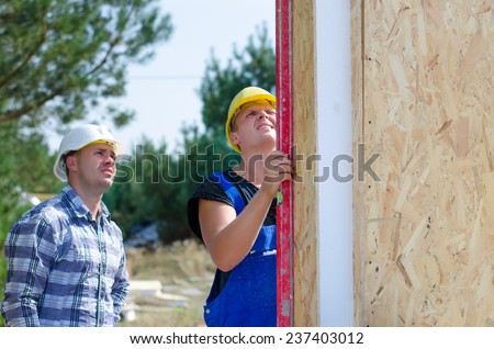 Two builders installing insulated wooden wall panels on site checking with a builders level to see that they are vertical - stock photo