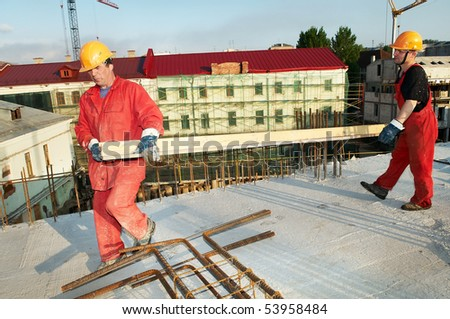 two builders workers carrying wood board at construction site - stock photo