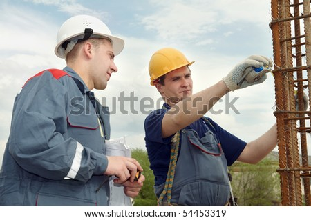 two builders workers checking with measure tape reinforcement column - stock photo