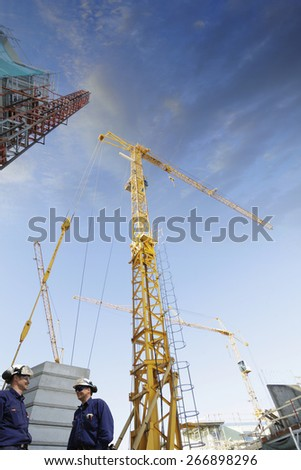 two building workers with construction cranes at sunset - stock photo