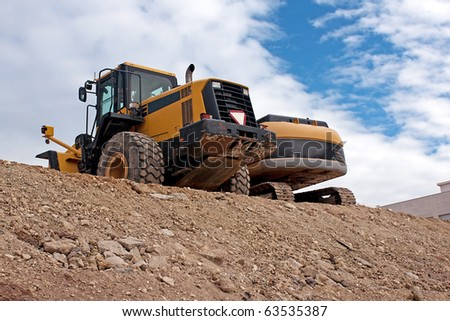 Two Bulldozers at the top of the slope - stock photo