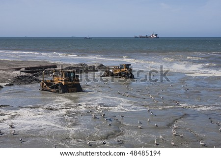two Bulldozers on the beach on a dredging project in holland with dredger in background - stock photo