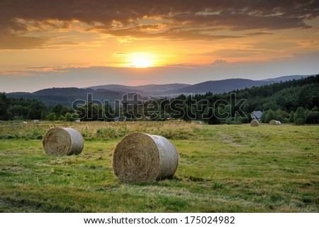 Two bundles of the straw on the meadow during the sunset - stock photo