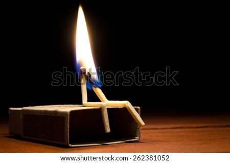 Two burning match humans sitting on a matchbox on a dark background - stock photo