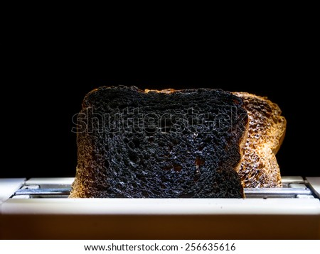 Two burnt toast slices sticking out of toaster over black background - stock photo