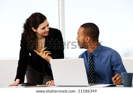 two business associates with a grey laptop - stock photo