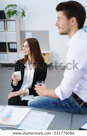 Two business colleagues, a man and attractive stylish young woman, sitting looking to the left of the frame wit attentive expressions as they relax over coffee and a glass of water - stock photo