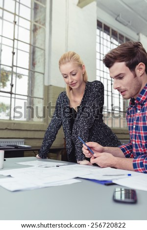 Two business colleagues, an attractive blond woman and man, at work in the office discussing paperwork spread out on the desk - stock photo