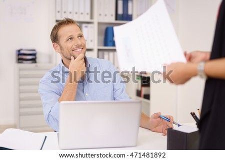 Two business colleagues chatting in the office with focus to an attractive smiling man looking up at a woman holding a document