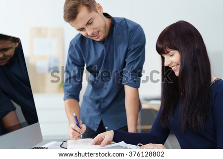 Two business colleagues discussing paperwork at a desk together with pleased smiles, man and woman - stock photo