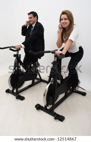 Two business colleagues riding exercise bikes and chatting on their cell phones. Isolated. - stock photo