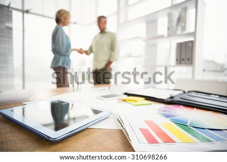 Two business colleagues shaking hands in the office - stock photo