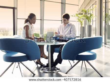 Two business colleagues sitting at a table, having a meeting - stock photo