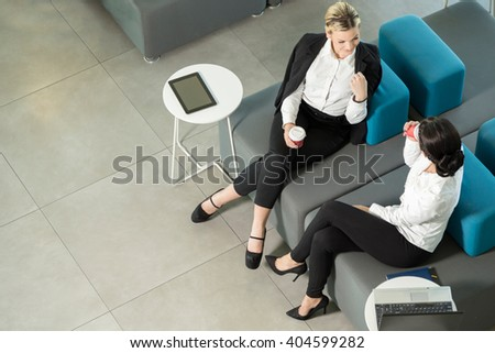 Two business colleagues sitting in a modern office building hallway on a coffee break - stock photo