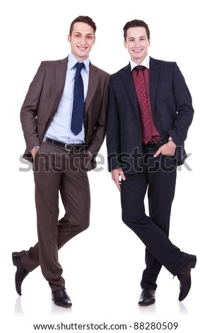 two business friends standing shoulder to shoulder and with their hands in pockets - stock photo